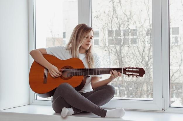 白いtシャツと灰色のレギンスを着た若い女性が窓辺に座ってアコースティックギターを弾いています。