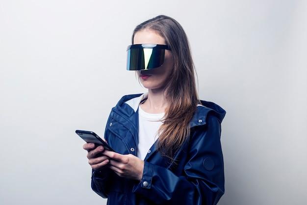 가상 현실 안경을 쓴 젊은 여성이 밝은 배경에 전화기를 들고 있습니다.