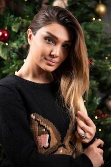 座ってカメラを見ている暖かいセーターを着た若い女性。高品質の写真