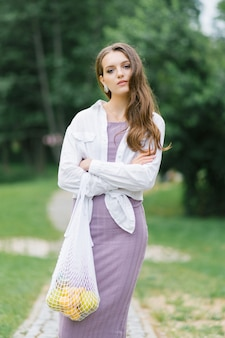 Молодая женщина в бело-сиреневой одежде с эко-сумкой с фруктами на фоне природы. концепция без пластика
