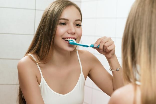 若い女性がトイレで歯を磨いています。鏡の反射。