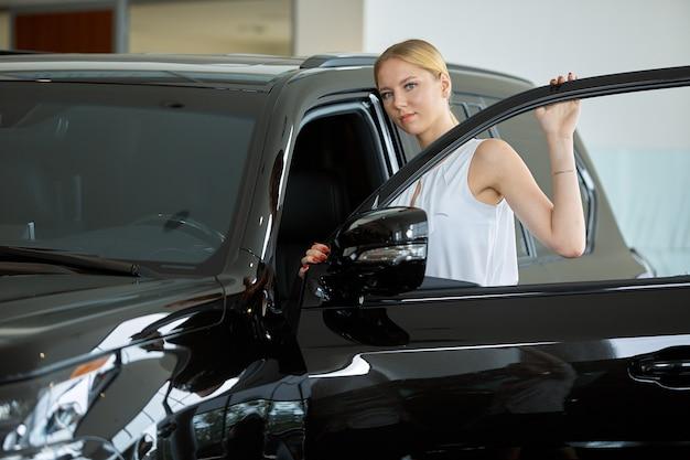 若い女性がディーラーで車を買うことを考えています