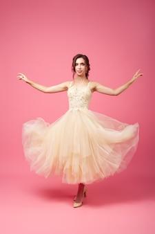 若い女性は袖のない長いベージュのボールガウンでブルネットの緑豊かなドレスを着て踊っています...