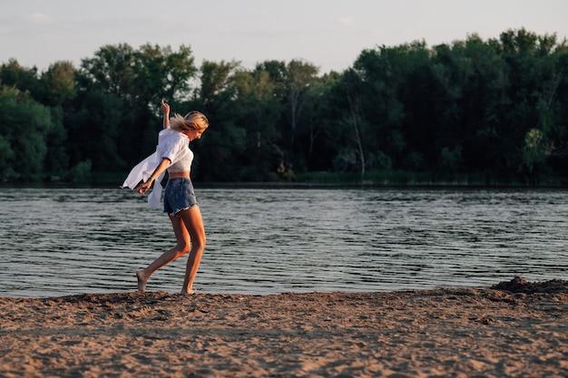 若い女性が川岸で白いシャツとデニムのショートパンツで幸せな美しいブロンドを踊っています...