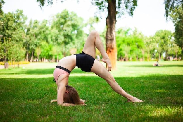 若い女性が自然の中でヨガの練習をしています。
