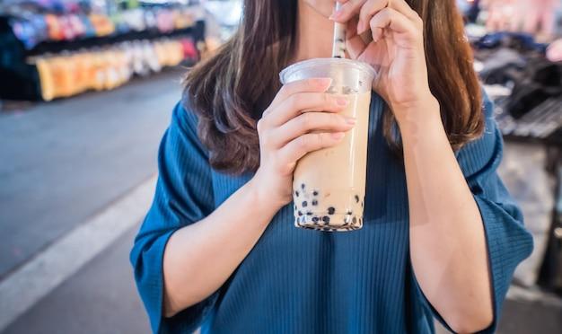 若い女性が台湾のナイトマーケットでストローと一緒にタピオカティーのプラスチックカップを飲んでいます。台湾の珍味がクローズアップされています。