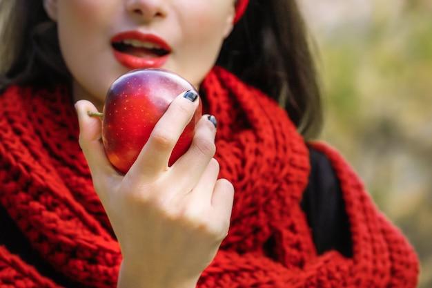 젊은 여자가 잘 익은 빨간 사과를 먹고 있다. 금단의 열매.
