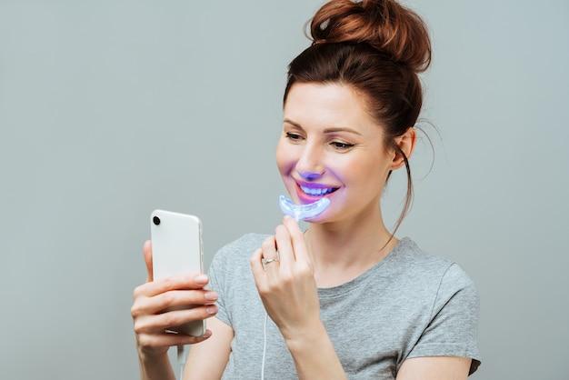 Молодая женщина занимается домашним отбеливающим комплексом для отбеливания зубов уф лампой