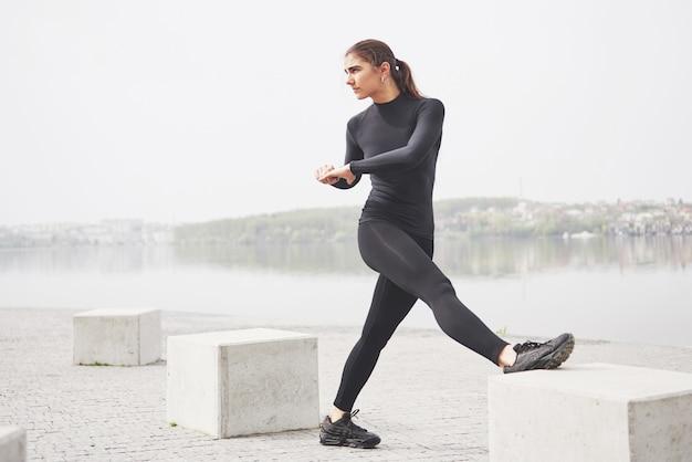 若い女性が公園の湖のほとりでスポーツに従事