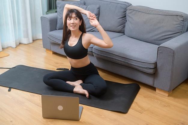 若い女性は、自宅の居間でラップトップでオンライントレーニングフィットネスクラス、スポーツ、フィットネス、テクノロジーのコンセプトを行使して見ています。