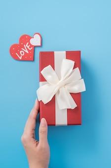 Молодая женщина делает подарок с биркой в форме сердца и текстом любви. валентина концепция
