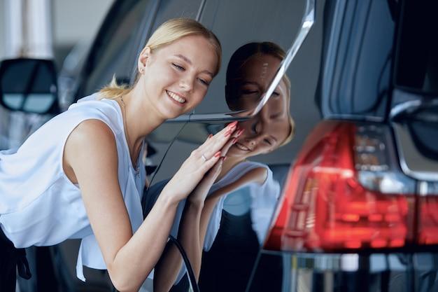 若い女性は、自動車販売店で車を購入する前に、自分の選択に満足しています。