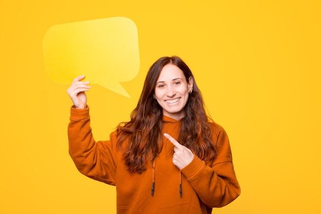 Молодая женщина держит речевой пузырь и показывает на него, улыбаясь