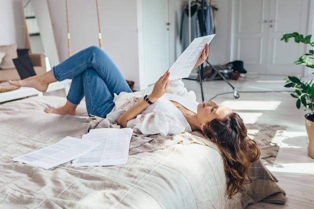 若い女性が寝室の読書のベッドに横たわっています。