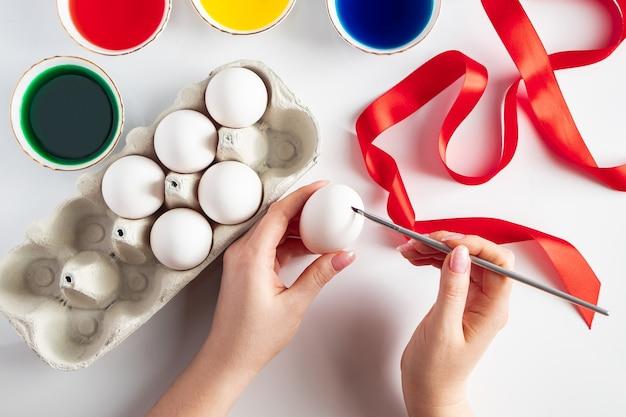 Молодая женщина рисует пасхальные яйца
