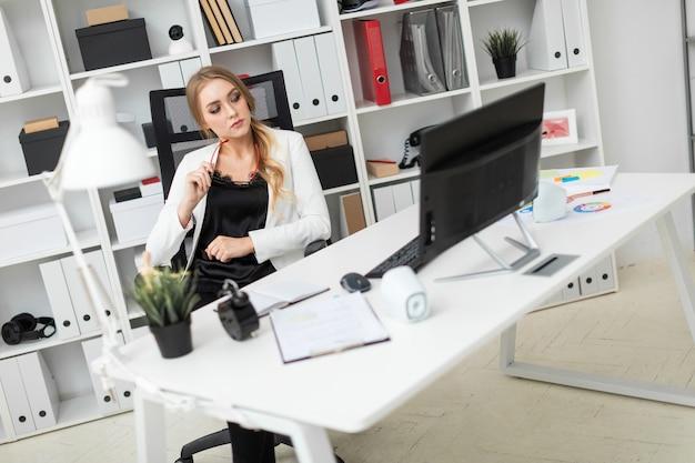 Молодая женщина сидит за столом в кабинете, держит в руке очки и смотрит на монитор.