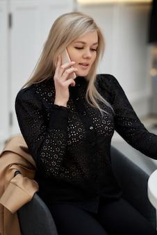 若い女性はショッピングセンターのカフェに座って、携帯電話でチャットし、紙コップのコーヒーを手に持っています。