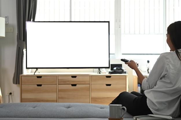 젊은여자가 소파에 앉아 집에서 텔레비전을 시청하는 원격 제어를 들고있다.