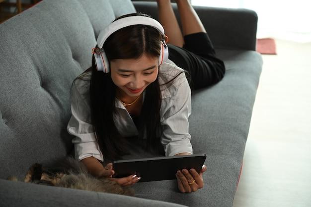 Молодая женщина сидит на диване и смотрит фильм на планшете.