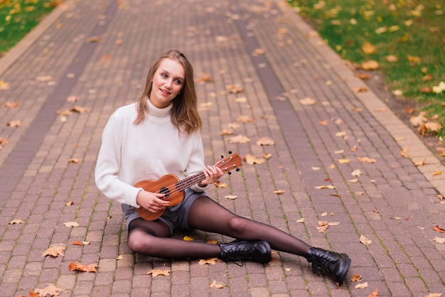 젊은 여성이 공원 벤치에 앉아 기타와 함께 포즈를 취하는 우쿨렐레를 연주하고 있습니다.