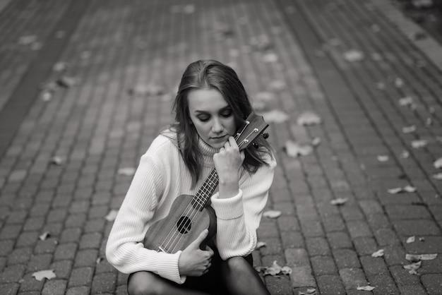 Молодая женщина сидит на скамейке в парке и играет на укулеле, позирует с гитарой