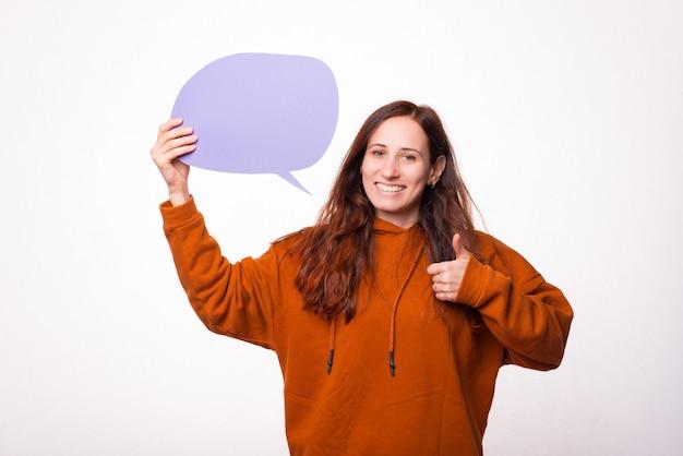 Молодая женщина улыбается в камеру, держит речевой пузырь, показывает большой палец вверх