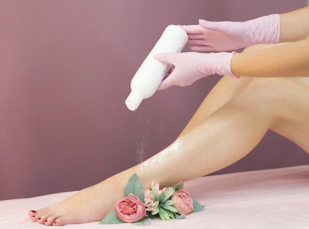 Молодую женщину присыпают пудрой на ноги без процедуры шугаринга.