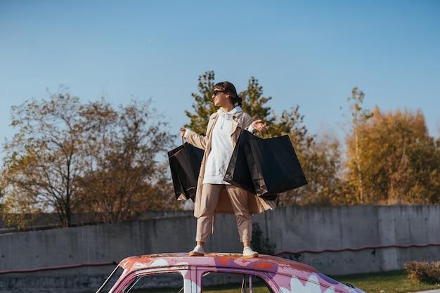 若い女性が手にバッグを持って車の中に立っています。