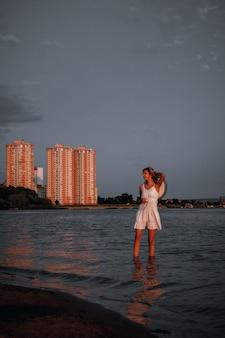 젊은 여자가 흰색 여름 레이스 드레스에 아름 다운 날씬한 행복 한 금발 물에 서 있습니다...