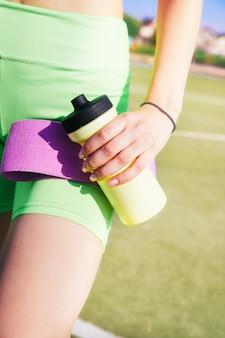 Молодая женщина стоит на спортивном поле. девушка держит в руках фитнес-резинку и бутылку с водой. спортсменка подготовилась к фитнесу.