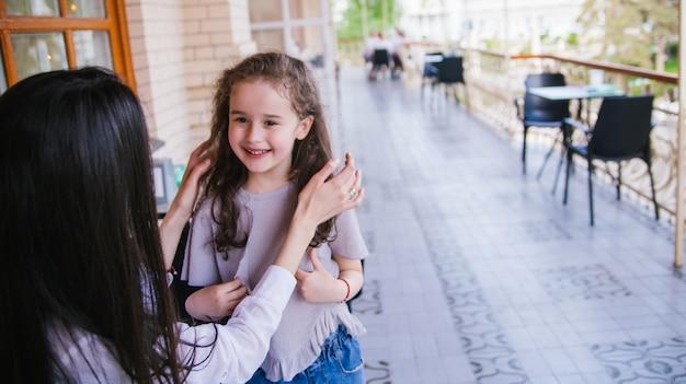 젊은 여자가 그녀의 어린 딸과 이야기하고 있습니다. 그 소녀는 어머니의 말을 주의 깊게 경청합니다.