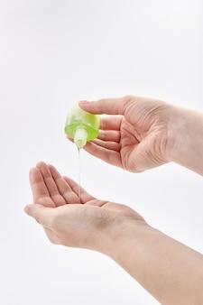 若い女性が手指消毒ジェルを使用しています。ウイルス性疾患の予防。