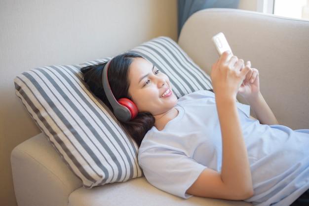 Молодая женщина использует гарнитуру, наслаждаясь музыкой в гостиной