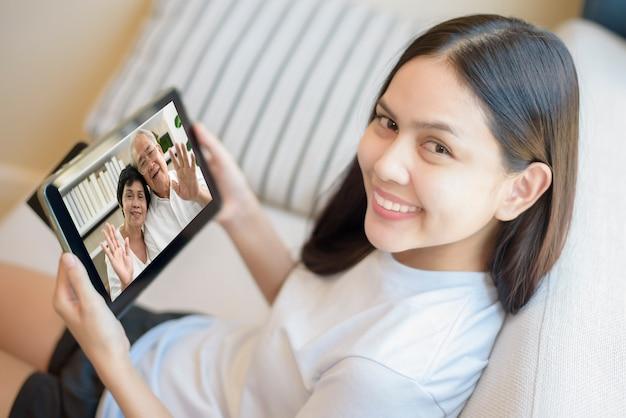 若い女性はタブレットをビデオ通話に、またはウェブカメラを祖父母、電気通信技術、親子家族の概念に使用しています。