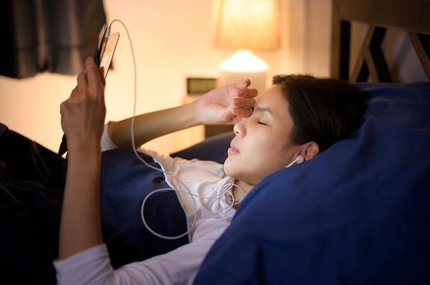 若い女性がタブレットを使用して、寝室で友人や家族に映画やビデオ通話を見て、常夜灯