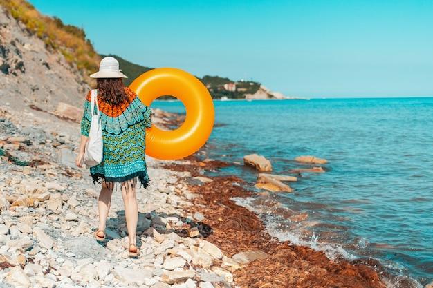 Молодая женщина идет по каменистому дикому пляжу с надувным кругом в руках.