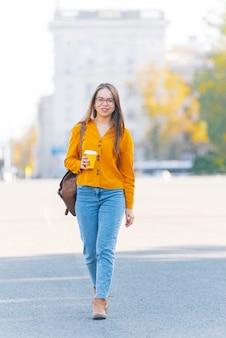 若い女性が手に温かい飲み物を持って歩いています