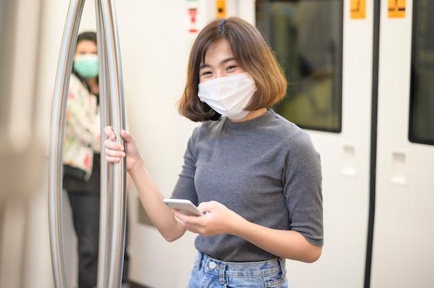 若い女性は、メトロで保護マスクを着用しています、covid-19保護、安全旅行、ニューノーマル、社会的距離、安全輸送、パンデミックの概念の下での旅行。