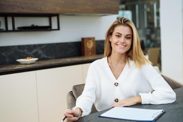 젊은 여자가 그녀의 부엌에서 일하고 노트북에 뭔가를 쓰고 있습니다. 사업가 집에서 원격으로 작동합니다.