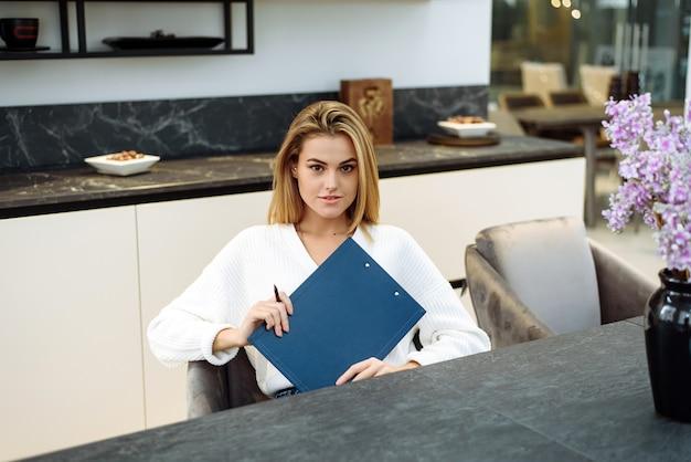 若い女性が台所で働いていて、ノートに何かを書いています。実業家は家から離れて働いています。