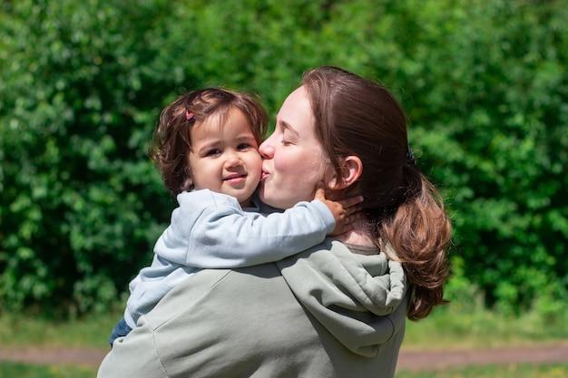 Молодая женщина целует ребенка в щеку, держа ее на руках