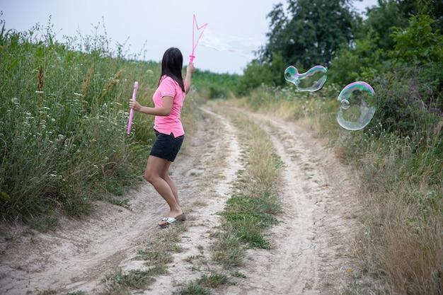 Молодая женщина запускает огромные мыльные пузыри на фоне красивой природы, вид сзади.