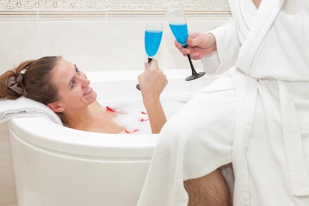 若い女性が泡と花びらの付いた浴槽に横たわり、白いコートを着た男性と青いシャンパンのグラスをチャリンと鳴らします。男性は浴槽の端に座っています。