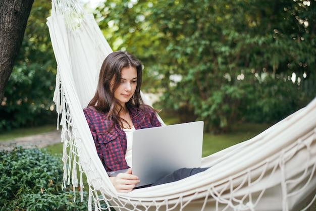 Молодая женщина лежит в гамаке с ноутбуком в саду и работает удаленно.