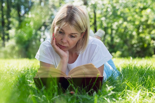 젊은 여자가 공원의 잔디에 누워 책을 읽습니다. 주근깨가 있는 예쁜 금발. 화창한 여름날에 휴식을 취하십시오.