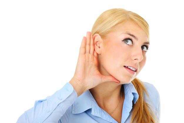 Молодая женщина слушает с вниманием на белом фоне