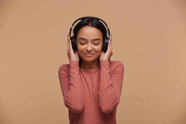 젊은 여성이 큰 검은 헤드폰으로 좋아하는 음악을 듣는다.