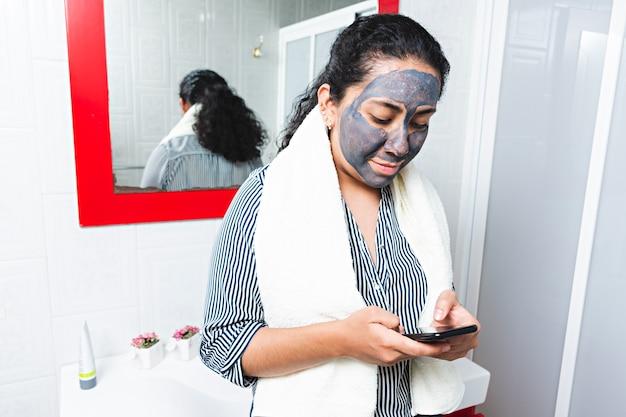 얼굴을 닦기 위해 기다리는 동안 스마트폰을 보고 있는 젊은 여성