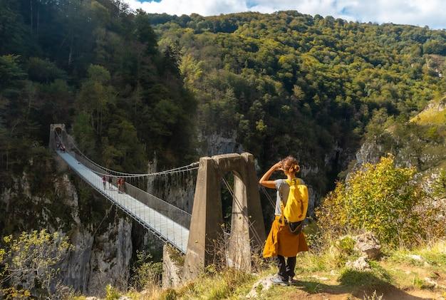 ラローのpasserelleholtzarteを見ている若い女性。スペインのナバラとピレネーアトランティックの北にあるイラティの森またはジャングルで