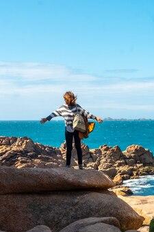 フランス、ブルターニュのコートダモール、ペロスギレックの町にあるプルマナッコ港の灯台ミーンルス沿いの海を見ている若い女性。
